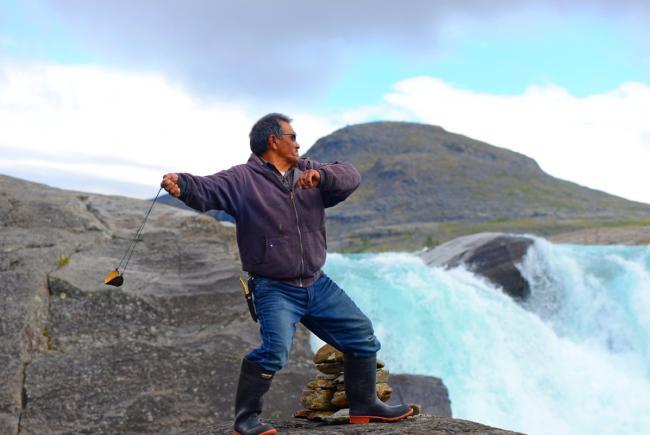 Lukassi Etoq and his slingshot at the edge of the Qurlutuarjuq Falls on the Koroc River, in Kuururjuaq National Park