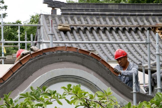 Réfection du Jardin de Chine - Été 2016 - Pose des tuiles sur les toits par les travailleurs chinois.