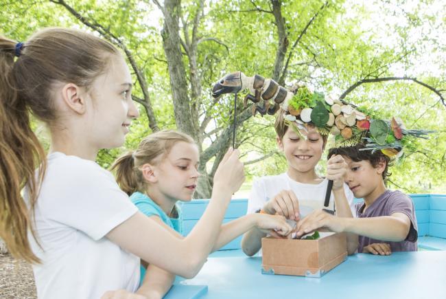 """Des enfants s'amusant avec une marionnette de phrygane au cours du parcours immersif """"La nature pour toit""""."""