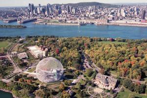 Vue aérienne de l'Île Sainte-Hélène et de la Biosphère avec le centre-ville de Montréal en arrière-plan.