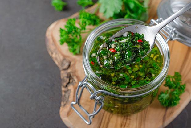Un pot en verre avec une sauce chimichurri fraîche faite maison, posé sur une planche en bois avec des herbes sur fond vert