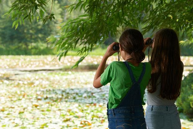 Deux jeunes filles regardent la nature avec des jumelles au Jardin botanique de Montréal